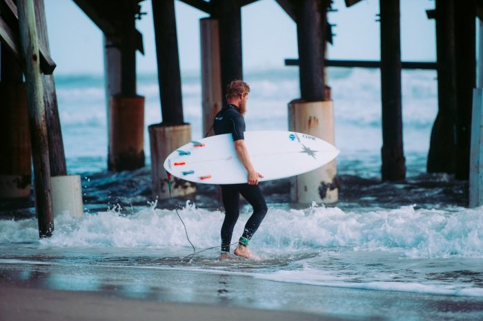A man getting ready to surf in Cocoa Beach
